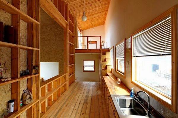 这是一栋利用原有单层平房改建和加建而成的周末别墅。原有的结构为砖混单层坡顶,现在将原有坡顶去掉,利用原来的墙体和新加设的轻型木结构墙体,加建为一个局部三层的混合结构房屋。由于基地周围环境较为凌乱,所以将首层设计为不怕打扰的木工工房,将居住的功能提升到能够看到西侧果园和农田景观的二层,三层设计了两个阁楼空间和户外平台。住宅的内部功能分成几个平台,沿着围绕二层中庭螺旋上升的流线展开,从一楼的工房,到二层的餐厅,起居室,厨房,最后到三层的阁楼和户外平台。平台间的高差设计成使得有些台面既是地板又是宽大的坐席,可以